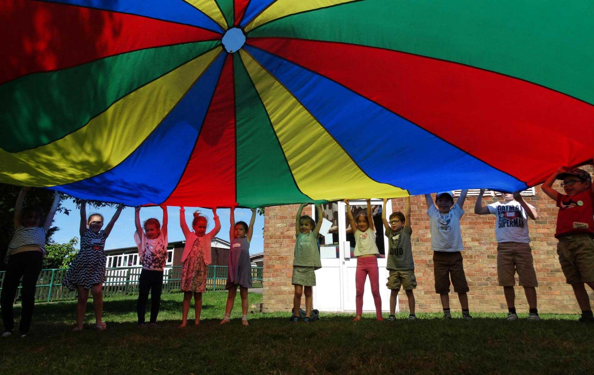 Children playing with parachute over summer at mini minors