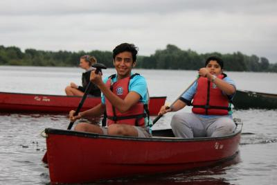 Teen boys having fun canoeing at XUK Summer Camp