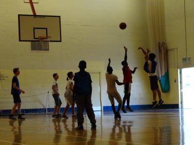 Teenagers playing basketball at UK summer camp