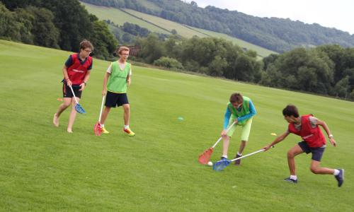 Teenagers playing lacrosse at summer camp