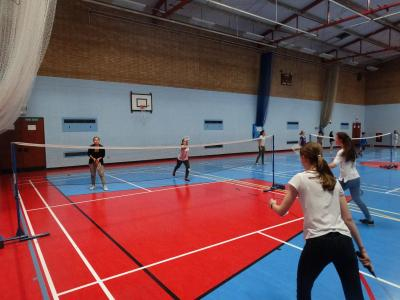 Teenagers playing badminton at English school