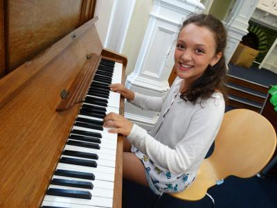 Girl playing piano at English summer school