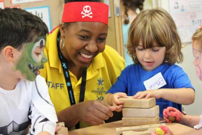 Staff and kids playing with bricks at day camps London