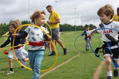 Children running through hoops at London day camp