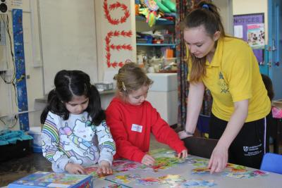 Kids building puzzles with staff at Mini Minors