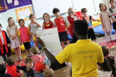 Children singing in talent show for summer London camp
