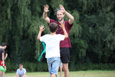 staff member and camper high five sports session at multi activity summer camp in UK