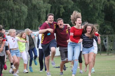 Staff member laughing and having fun running at summer residential camp