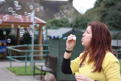 Happy staff member blowing bubbles in playground at north london play scheme day camp