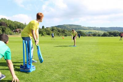 teenage boys playing cricket during sports session at uk residential summer camp