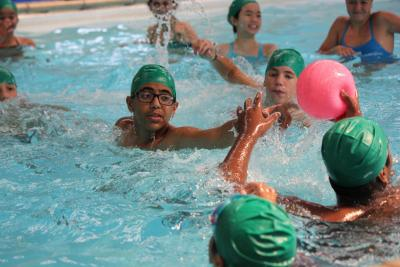 campers playing water polo in swimming pool at activity summer camp in uk