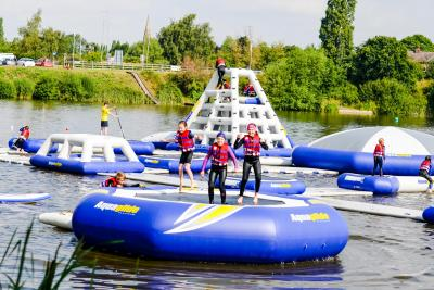 children and teenagers at aqua park on summer camp trip in britain