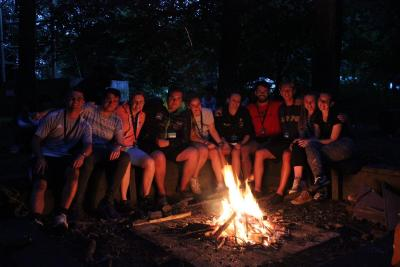 summer camp staff in great britain sat around camp fire english speaking camp uk