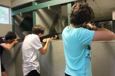 male campers shooting rifles at british summer camp in london
