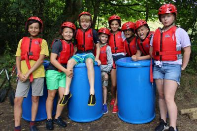 children and teenagers raft building and racing at british english speaking uk summer camp