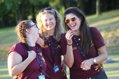 Summer camp staff laughing having fun holiday job