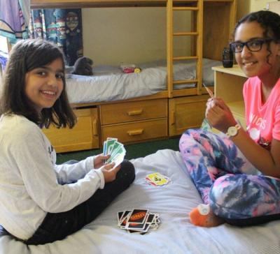 girls in dormitory playing cards sleep away camp uk for activities
