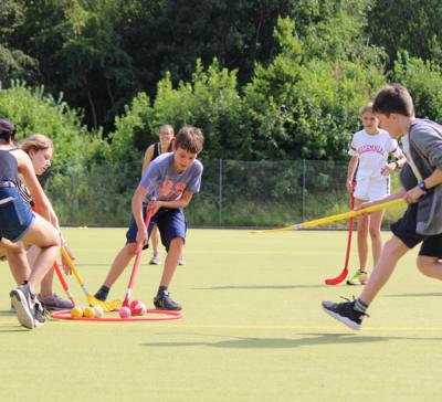 boys playing uni hoc at british summer camp uk